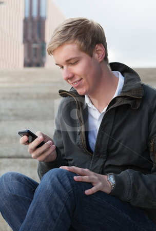 Sending an SMS stock photo, Young blond handsome smiling man texting with his mobile phone by Mikhail Lavrenov