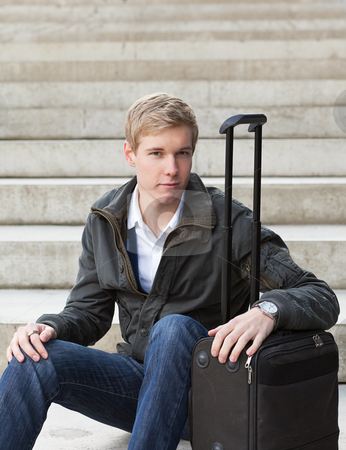 Young blond man with suitcase stock photo, Young blond handsome guy sitting on the stairs with his suitcase by Mikhail Lavrenov