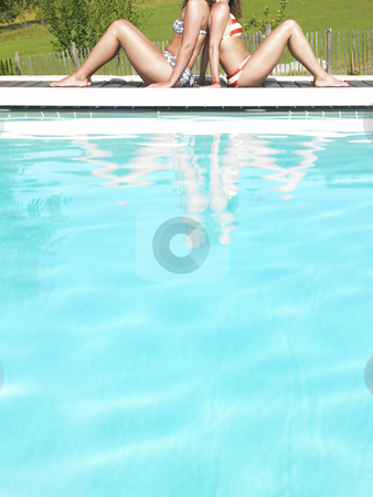 Cropped View of Two Women by Pool stock photo, Cropped view of two women sitting back to back next to pool. Vertically framed shot. by Mog Ddl