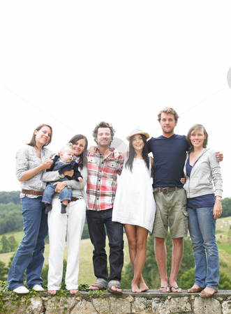 Group of Friends Standing Outdoors stock photo, Group of young people, with one woman holding a baby, standing on a stone wall outdoors. Vertical. by Mog Ddl