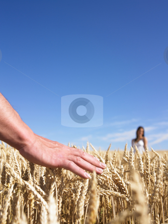 Hand & couple in wheat field stock photo, Close-up of men's hands with woman in background by Mog Ddl