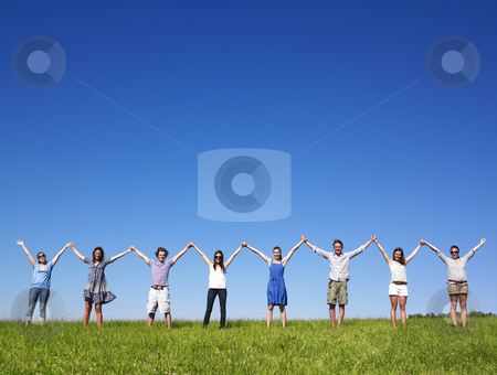 Group Holding hands stock photo, Group of friends holding hands in meadow under blue sky by Mog Ddl