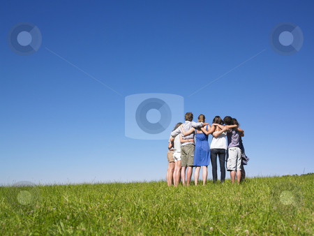 Group of People in Huddle in Field stock photo, A group of people huddle in a field. Horizontally framed shot. by Mog Ddl