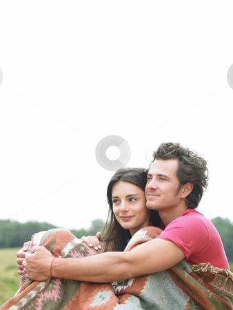 Couple Hugging Outdoors stock photo, Man wraps arms around woman as they sit together outdoors. Vertical. by Mog Ddl