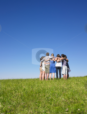 Group of People in Huddle in Field stock photo, A group of people huddle in a field. Vertically framed shot. by Mog Ddl