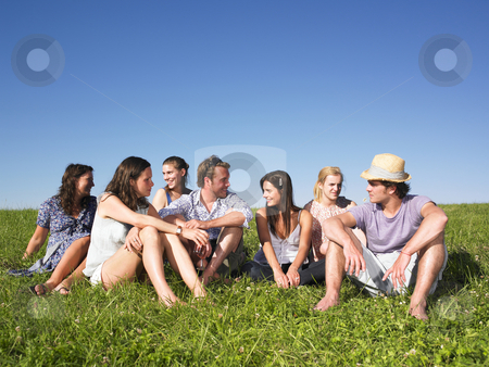 Group sitting in meadow stock photo, Group of friends sitting in meadow under blue sky by Mog Ddl