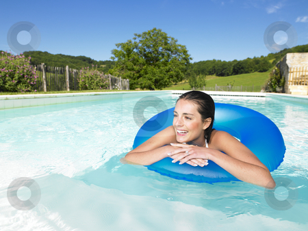 Smiling Woman Floating in Pool stock photo, Woman floating in inner tube in pool and smiling. Vertical by Mog Ddl