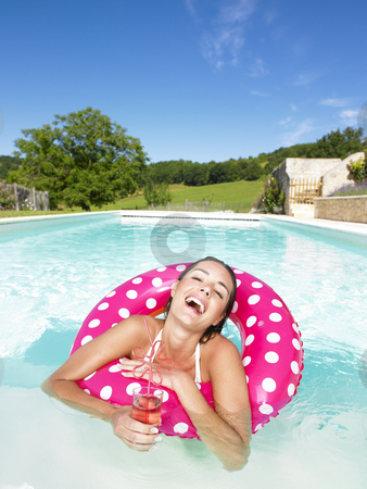 Laughing Woman in Pool With Beverage stock photo, Woman floating in an inner tube in a swimming pool and laughing with drink in hand. Vertical. by Mog Ddl