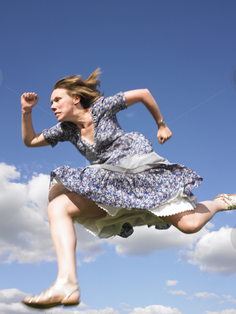 Woman Running in Dress stock photo, Woman running with sky as background. Vertically framed shot by Mog Ddl