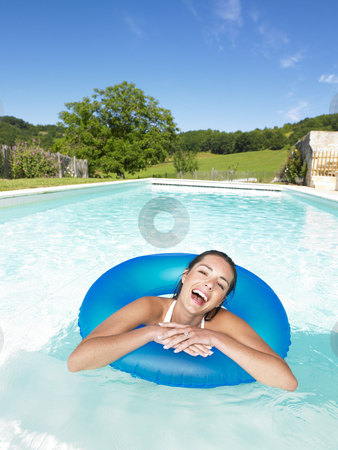 Laughing Woman Floating in Pool stock photo, Woman floating in inner tube in pool and laughing. Vertical by Mog Ddl
