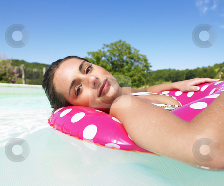 Serene Woman Floating in Pool stock photo, Woman floating in a pink polka dot inner tube and smiling gently at the camera. Horizontal. by Mog Ddl