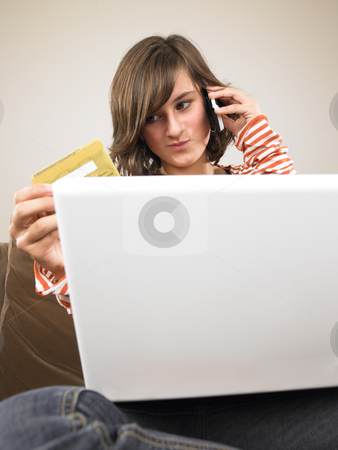 Young Woman With Laptop, Shopping Via Phone stock photo, Young woman with laptop, holding credit card and talking on the phone. Vertically framed shot. by Mog Ddl