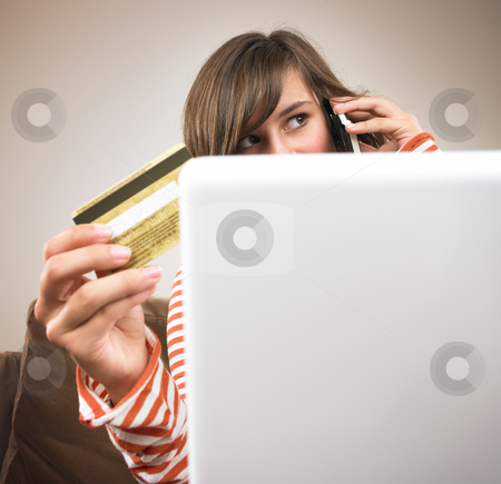 Young Woman Shopping via Phone stock photo, A young woman sits in front of a laptop, holding her credit card and talking on the phone. Square format. by Mog Ddl