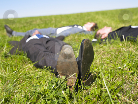 Businessmen Lying in the Grass stock photo, Three businessmen lying in the grass. Horizontal. by Mog Ddl