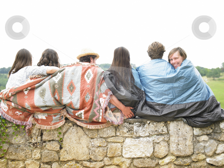 Friends Sitting Together on Stone Wall stock photo, Group of young people outside, sitting huddled under blankets, with one woman turning and smiling at the camera. Horizontal. by Mog Ddl