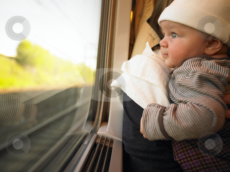 Baby Looking out Train Window stock photo, Baby looking out train window while being held by adult. Horizontally framed shot. by Mog Ddl