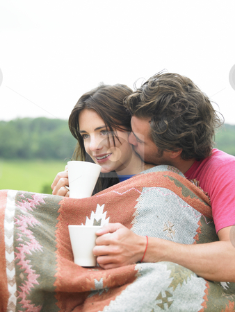 Couple Snuggling and Drinking Tea stock photo, Affectionate couple drinking tea outdoors. Vertical. by Mog Ddl