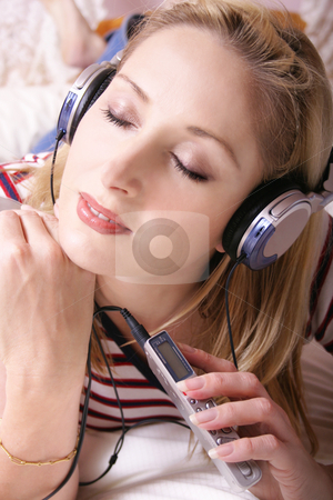 Woman on bed with muisc player stock photo, Girl with her musicc player and headphones chills on the bed. by Leah-Anne Thompson
