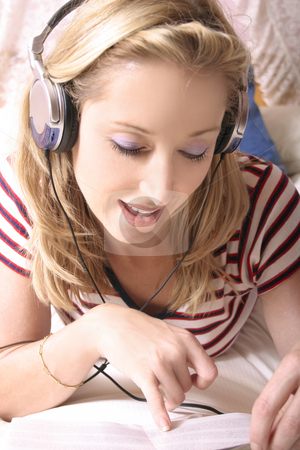 Girl listening to Music stock photo, Listening to music and reading the cd jacket by Leah-Anne Thompson