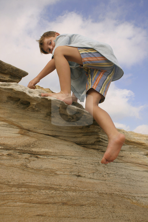 Clambering over rocks stock photo, Child clambering over coastal rocks by Leah-Anne Thompson