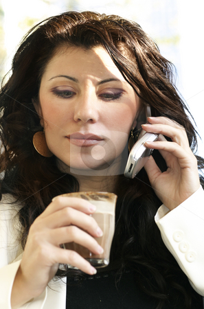 Woman on phone at cafe stock photo, Attractive businesswoman listening mobile at cafe - shallow dof focus to face. by Leah-Anne Thompson