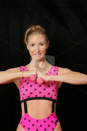 Exercise and fitness.  Firm upper body stock photo, Firm upper body - young woman firming upper body and arms.  Dark background space for copy by Leah-Anne Thompson