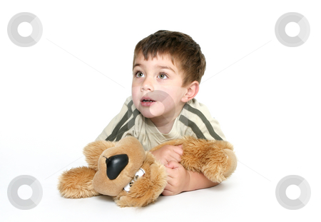 Child holding a plush toy stock photo, Child dressed in casual clothes,  laying on the floor holds closely a plush toy dog.  He is looking up, space for text. by Leah-Anne Thompson
