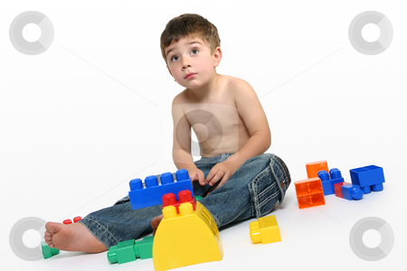 Young boy amongst building blocks stock photo, Young boy sits amongst colourful generic building blocks. by Leah-Anne Thompson