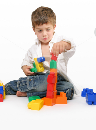 Child's concentration stock photo, Toddler playing with generic building blocks. by Leah-Anne Thompson