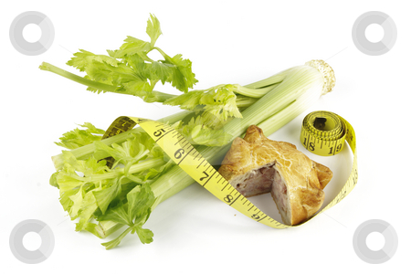 Celery with Pork Pie and Tape Measure stock photo, Contradiction between healthy food and junk food using celery and pork pie with a tape measure on a reflective white background by Keith Wilson