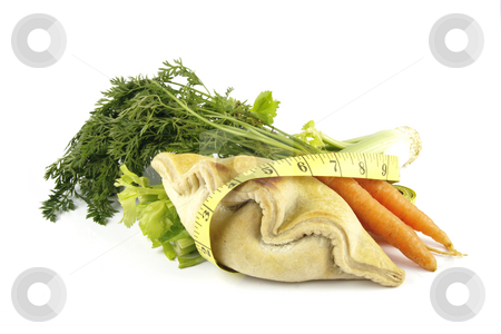 Carrots with Celery and Pasty stock photo, Contradiction between healthy food and junk food using a bunch of carrots and pasty with a tape measure on a reflective white background by Keith Wilson