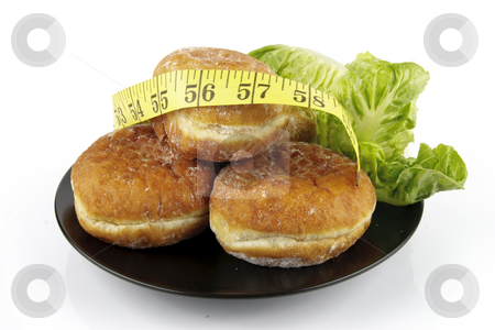 Doughnuts and Lettace with Tape Measure stock photo, Contradiction between healthy food and junk food using doughnuts and lettace with a tape measure on a reflective white background by Keith Wilson