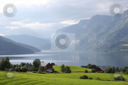 Norwegian landscape stock photo, Green sunlit meadows with a lake and mountains in the background. A typical norwegian landscape. by Anders Peter