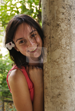 Teenage girl smiling stock photo, A young teenage girl with long brown hair and  with a flower on her ear smiling and pretending to hide behind a brick column. Photo taken on the 28th of September, 2009. by Alessandro Rizzolli