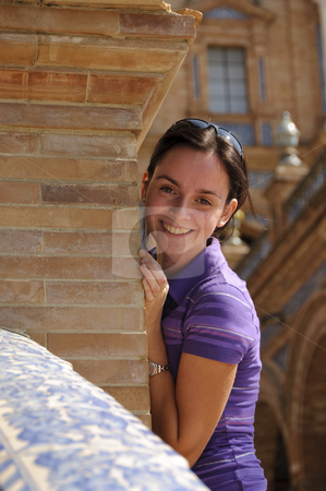 Young girl smiling and hiding stock photo, A young teenage girl with brown hair smiling and pretending to hide behind a brick column. Photo taken on the 27th of September, 2009. by Alessandro Rizzolli