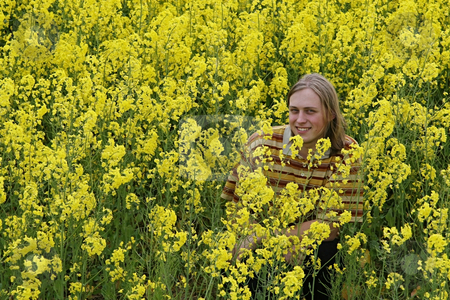 Smiling man in meadow stock photo, Happy and smiling young man in the yellow flower meadow. by Roberts Ratuts