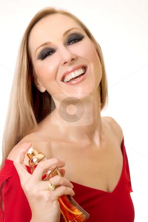 Smiling woman spraying perfume stock photo, A smiling woman spraying perfume to her neck area. by Leah-Anne Thompson
