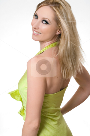 Smiling girl glances over shoulder stock photo, Smiling confident female wearing a lime green halter dress glances over her shoulder. by Leah-Anne Thompson
