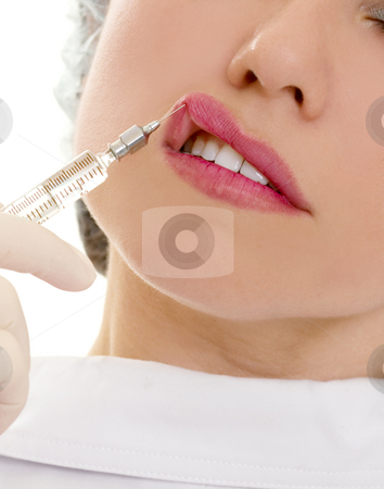 Lip Augmentation stock photo, Lip augmentation performed under local anesthesia will enhance or restore a fuller shape to lips.  The most common way to increase lip size is with injectable fillers such as collagen, restylane, fat, hyaluronic acid, aquamid or goretex. by Leah-Anne Thompson
