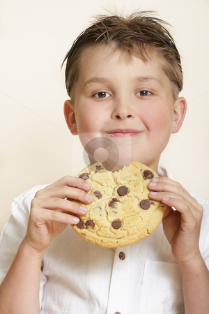 Monster cookie stock photo, Boy with large cookie and smiling by Leah-Anne Thompson