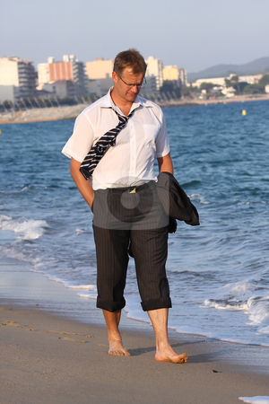 Unemployed stock photo, A sad businessman is walking on the beach by ARPAD RADOCZY