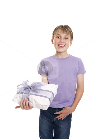 Smiling boy holds a gift wrapped present stock photo, Excited  boy in plain t-shirt and jeans holding a wrapped present ready for birthday or other special occasion. by Leah-Anne Thompson
