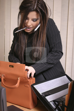 Multi Tasking - Busy Businesswoman stock photo, A hectic work day.   Businesswoman on the phone to a client while organising files and bags at the same time    This could be a lawyer, accountant or other business professional. by Leah-Anne Thompson
