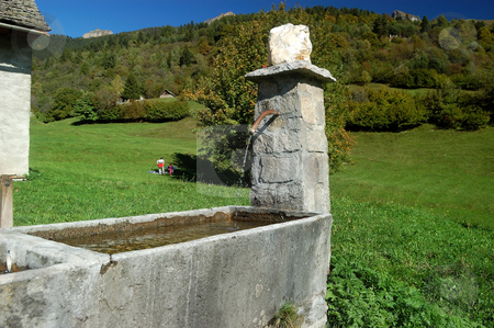 Stone fountain stock photo, Stone fountain in an Italian alpine village by ALESSANDRO TERMIGNONE