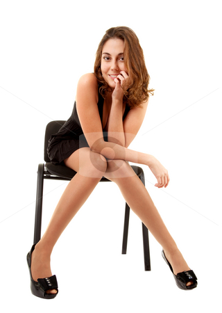 Women in black dress on chair stock photo, Beautiful smiling women in black dress is sitting on a chair on white background by Iryna Rasko