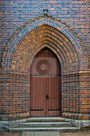 Arched church doorway stock photo, An arched brick doorway with wooden door leading into the church by Phil Morley