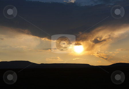 Mountainous Dusk stock photo, Sun peering through rain clouds over a mountain range in South Africa at dusk by Chris Alleaume