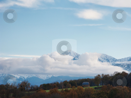 Mountain landscape stock photo, Pyrenees mountains range in clouds with field in the foreground by Laurent Dambies
