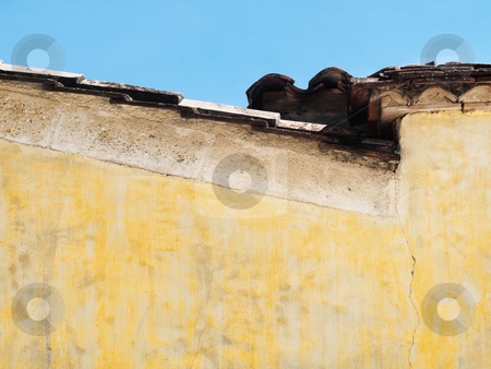 Roof stock photo, Side view of a roof with yellow vintage wall under blue sky by Laurent Dambies