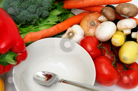 Empty Soup Bowl stock photo, White bowl surrounded by fresh vegetables that can be used to make vegetable soup including carrots, bell pepper, mushrooms, onions, and other produce by Lynn Bendickson